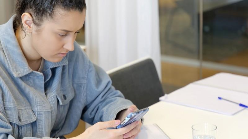 Gymnasieelev läser på sin mobil.